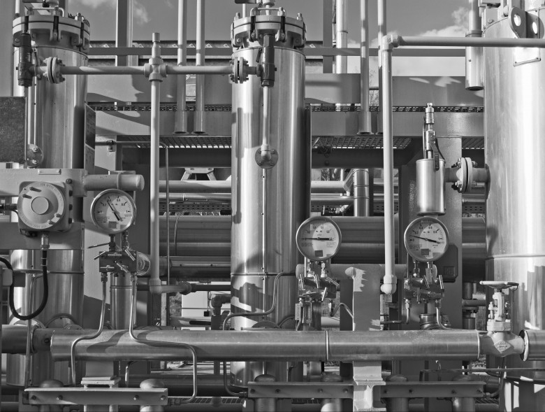 Close up of a modern natural gas processing plant with pressure dials on gasworks pipes